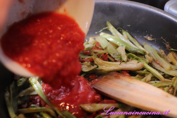Dopo un paio di minuti aggiungere la passata di pomodoro e cuocere per una decina di minuti.