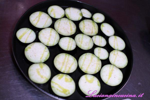 Ungere leggermente il piatto crisp del microonde (oppure una teglia da forno), adagiare le fette di melanzana ed ungere anche la superficie.