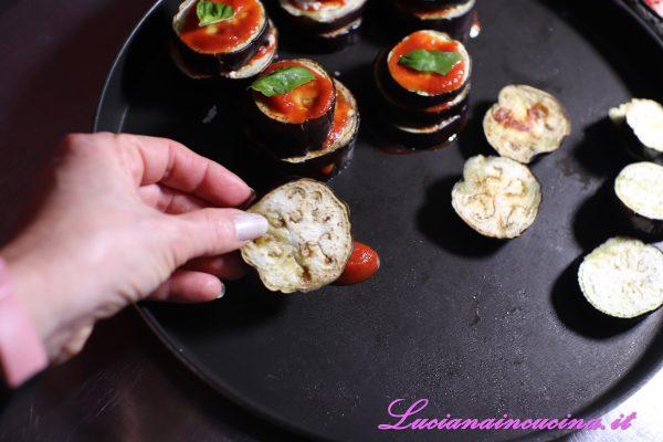 A questo punto passare all'assemblaggio delle torri di melanzane: versare una cucchiaiata di salsa di pomodori sul fondo della teglia, coprire con una fetta di melanzana, aggiungere un cucchiaio di salsa di pomodoro.