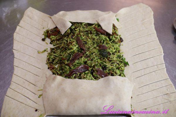 Tagliare la pasta intorno con tagli obliqui, poi intrecciare le strisce di impasto sul ripieno sigillandolo.