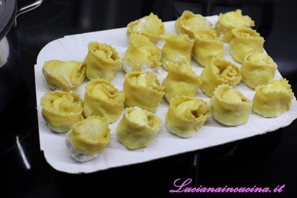 Incidere la pasta ottenendo dei cerchi che andranno piegati e sigillati dando la forma di un tortello.